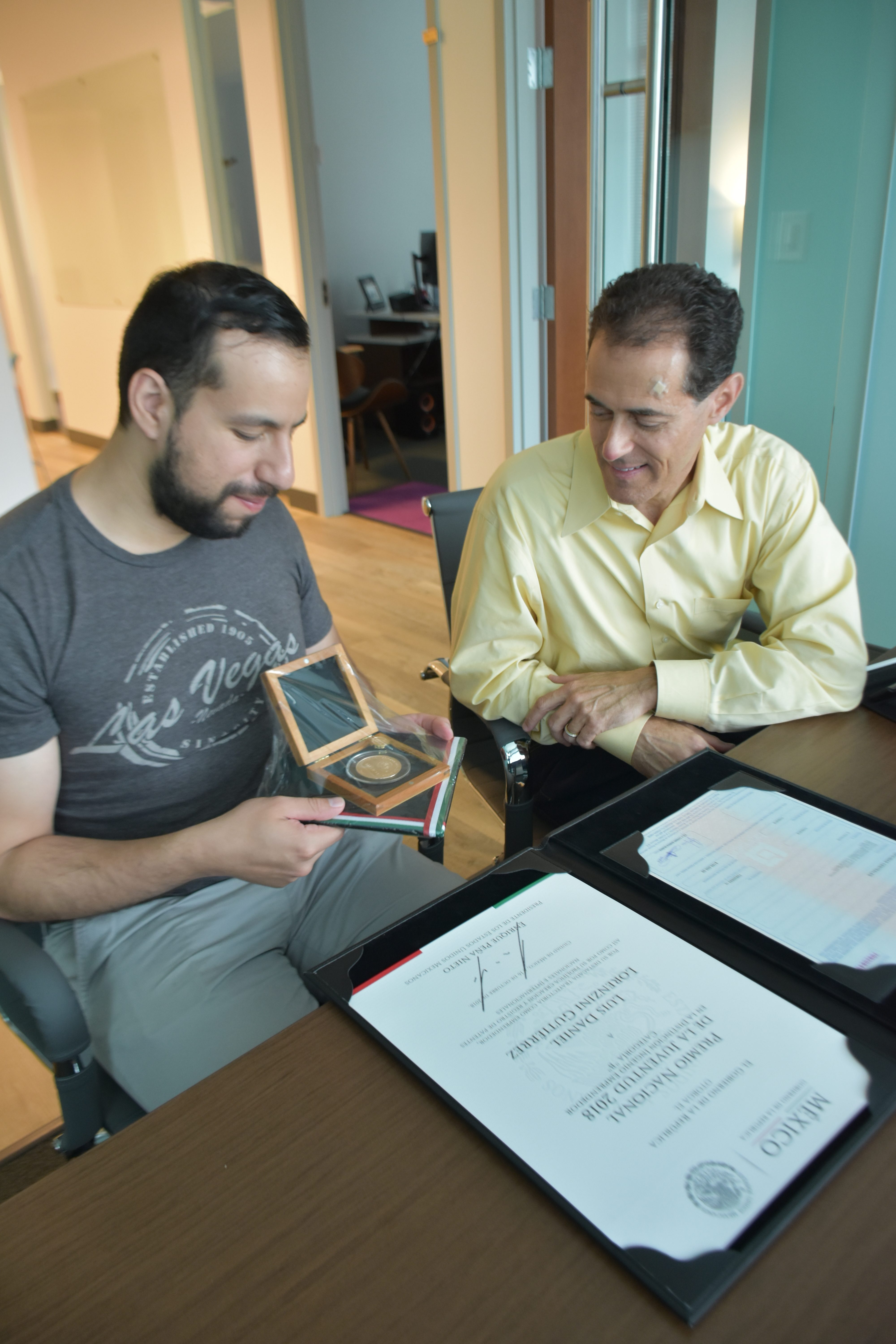 Daniel Lorenzini (left), founder of EMCOOL, shows Jonathan Goldman, a principal in Georgia Tech's VentureLab program, his entrepreneurship award he received from the Mexican government for his work in co-founding a startup in that country. (Péralte C. Paul)